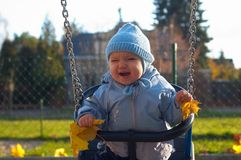 Baby. Portrait of happy baby on swing Royalty Free Stock Photo