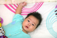 Baby. Cute oriental baby on bed Stock Photos