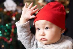 Baby. Cute baby boy in red hat holding his hand Royalty Free Stock Photography