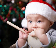 Baby. Holding a toy and wearing a santa hat in christmas eve Stock Image