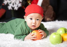Baby. Holding fruits at holiday s eve Royalty Free Stock Photo
