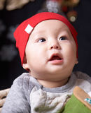 Baby. An asian child in a red hat against dark background Royalty Free Stock Photos