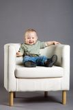 Baby. Photo of the baby sitting in an armchair on a grey background Stock Photography
