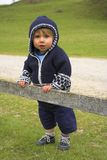 Baby. Boy stood against a fence Stock Photo