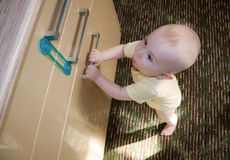Baby 8-9 months trying to open the door cupboard royalty free stock photography
