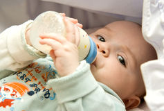 Baby. Drinking from a milk bottle Stock Image