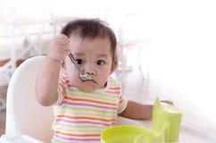 Baby aan het eten door die zelf wordt geprobeerd Royalty-vrije Stock Fotografie