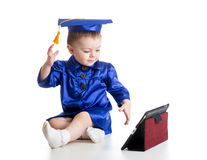 Baby with academic clothes playing tablet PC Stock Photo