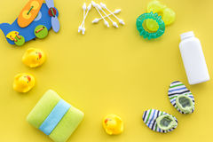 baby accessories for bath with body cosmetic and ducks on yellow background top view mock-up Stock Photos