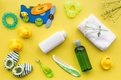 Baby accessories for bath with body cosmetic and ducks on yellow background top view pattern. Baby accessories for bath with body cosmetic and toy ducks on stock image
