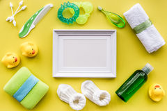 Baby accessories for bath with body cosmetic, frame and ducks on yellow background top view mock-up Royalty Free Stock Photography