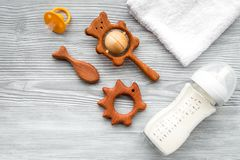 Baby accessories. Wooden toys, pacifier and bottle on grey wooden background top view copyspace. Baby accessories. Wooden toys, pacifier and bottle on grey Royalty Free Stock Photography