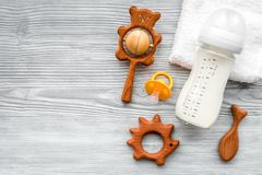 Baby accessories. Wooden toys, pacifier and bottle on grey wooden background top view copyspace. Baby accessories. Wooden toys, pacifier and bottle on grey Stock Images