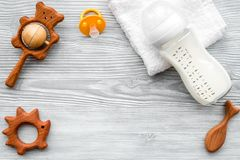 Baby accessories. Wooden toys, pacifier and bottle on grey wooden background top view copyspace. Baby accessories. Wooden toys, pacifier and bottle on grey royalty free stock image