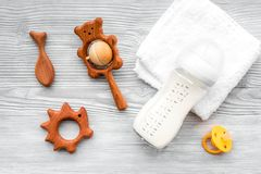 Baby accessories. Wooden toys, pacifier and bottle on grey wooden background top view.  Royalty Free Stock Images