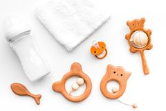 Baby accessories. Wooden toys, pacifier and bottle on white background top view.  Stock Image