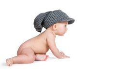 Baby in the adult winter hat crawling Stock Photo