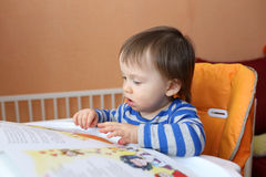 Baby age of 16 months reading book Stock Photography
