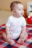 Baby age of 7 month sits on a floor and looks away Stock Images