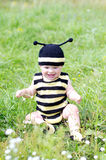 Baby age of 10 months in bee costume outdoors Stock Photo