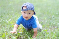 Baby age of 10 months creeps on grass in summer Royalty Free Stock Photo