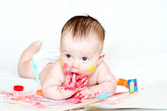 Baby age of 4 months draws finger-type paints Royalty Free Stock Photo