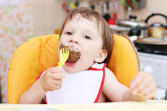 Baby age of 20 months eating. Meat Royalty Free Stock Images