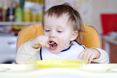 Baby age of 15 months eats Stock Photo