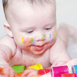 Baby age of 4 months with finger-type paints Stock Photo