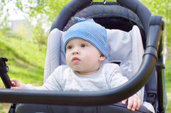 Baby age of 8 months outdoors on baby carriage Royalty Free Stock Photo