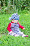 Baby age of 10 months plays sitting on grass in park Stock Image