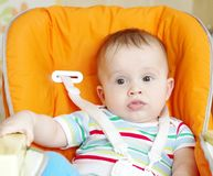 Baby age of 6 months sits on babies chair Stock Images