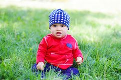 Baby age of 11 months sitting on grass. Outdoors Stock Photo