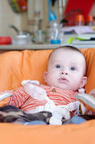 Baby age of 5 months sitting on highchair. Lovely baby age of 5 months sitting on highchair Royalty Free Stock Photos