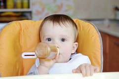 Baby age of 1 year drinks from small bottle Stock Photo