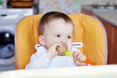 Baby age of 1 year eating bread Stock Photography