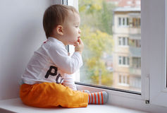 Baby age of 1 year looks out of window Royalty Free Stock Photo