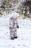 Baby age of 1 year walks on first snow Royalty Free Stock Photo