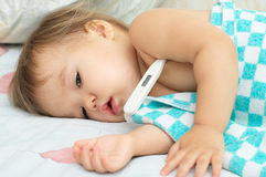 Baby ailing and lying with thermometer Stock Image