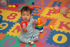 Baby on alphabet mat Royalty Free Stock Photos