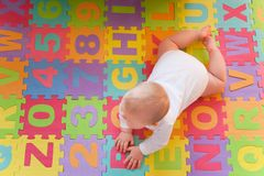Baby on alphabet mat stock photography