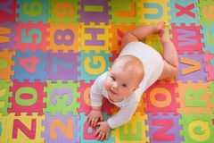 Baby on alphabet mat stock images