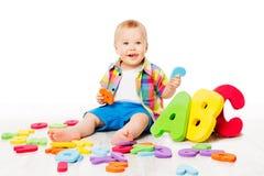 Baby-Alphabet-Spielwaren, Kind, das bunte ABC-Buchstaben auf Weiß spielt stockfotografie