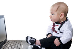 Baby with amazement looking at. Three-month baby in a suit businessman with amazemant looking at computer screen royalty free stock image