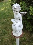 Baby angel - sculpture in the garden at Hodos-Bodrog Monastery  - Arad, Romania. Baby angel stand on a pedestal of stone - garden statue at Hodos-Bodrog Royalty Free Stock Image