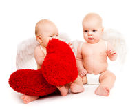 Baby angels. Two angelic baby friends in white diapers holding red heart Stock Image