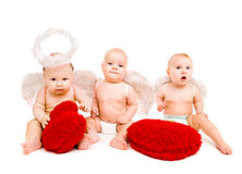 Baby angels. Three beautiful angels play with soft red hearts Royalty Free Stock Photo