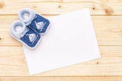 Baby announcement card with baby blue shoes. Stock Photo