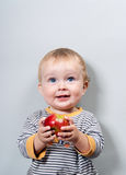 Baby with apple. Charming baby with apple on a grey background Stock Photography