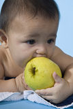 Baby with apple. Small charming baby with an apple Stock Photos